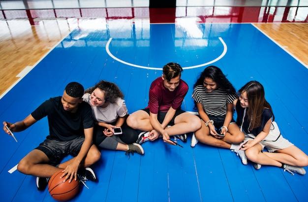 Groupe de jeunes amis adolescents sur un terrain de basket relaxant et utilisant un smartphone