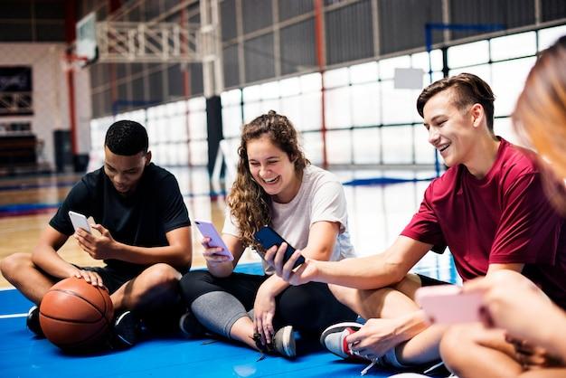 Groupe de jeunes amis adolescents sur un terrain de basket se détendre et à l'aide de smartphone
