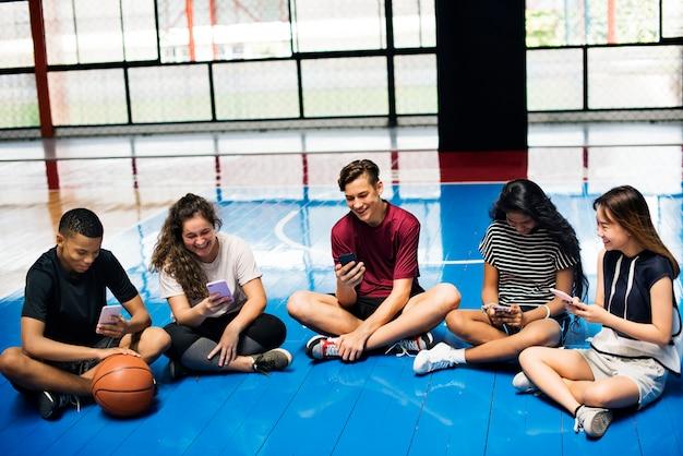 Groupe de jeunes amis adolescents sur un terrain de basket
