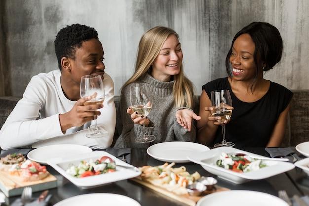Groupe de jeunes amis appréciant le dîner ensemble