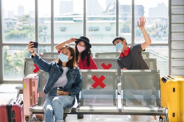 Groupe de jeunes amis asiatiques avec un masque facial selfie aux sièges d'attente du terminal de départ de l'aéroport. ils attendent de partir en vacances. voyage de sécurité avec distance sociale pour empêcher le delta de covid-19