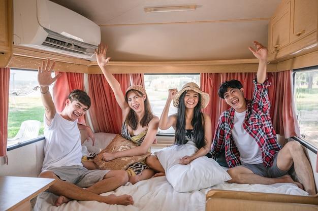 Groupe de jeunes amis asiatiques s'amusant à l'intérieur du camping-car le week-end