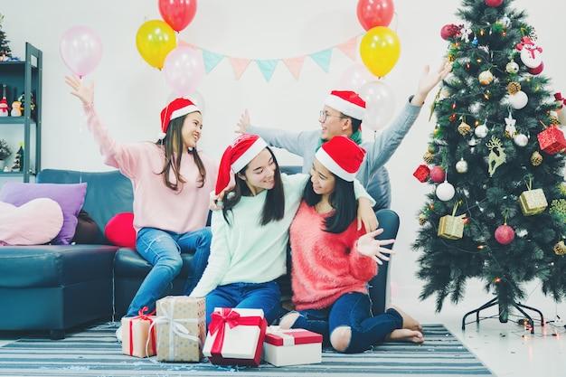 Groupe de jeunes amis assis à côté d'un arbre de noël joliment décoré
