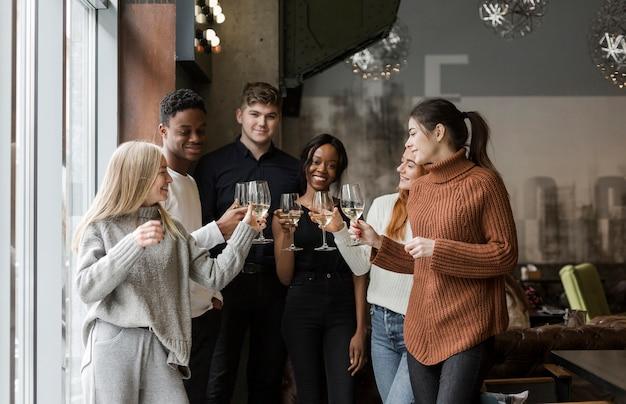 Groupe de jeunes amis ayant du vin ensemble
