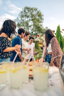 Groupe de jeunes amis cuisinant des saucisses et s'amusant dans un barbecue d'été en plein air