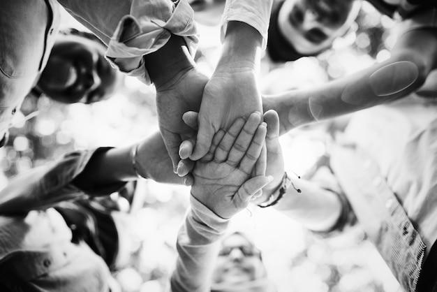 Groupe de jeunes amis empilant les mains