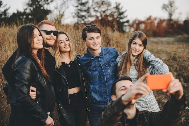 Groupe de jeunes amis étreignant et souriant tout en prenant selfie.