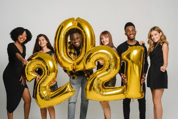 Un groupe de jeunes amis fête noël. des jeunes diversifiés détiennent des numéros 2021