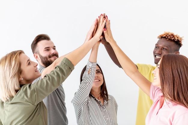 Groupe de jeunes amis haut cinq dans les airs