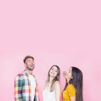 Groupe de jeunes amis heureux sur fond rose