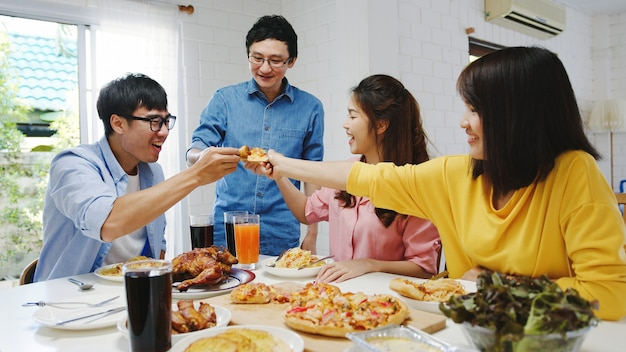 Groupe de jeunes amis heureux en train de déjeuner à la maison. fête de famille en asie, manger de la pizza et rire en appréciant un repas assis à table à manger ensemble à la maison. célébration de vacances et de convivialité.