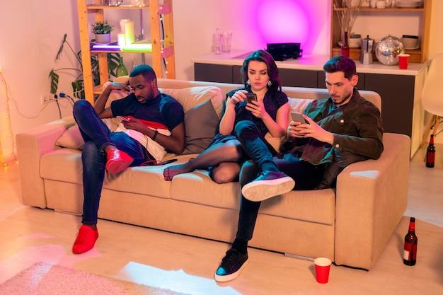 Groupe de jeunes amis interculturels assis sur un canapé moelleux dans le salon après la fête à la maison et en faisant défiler leurs gadgets mobiles