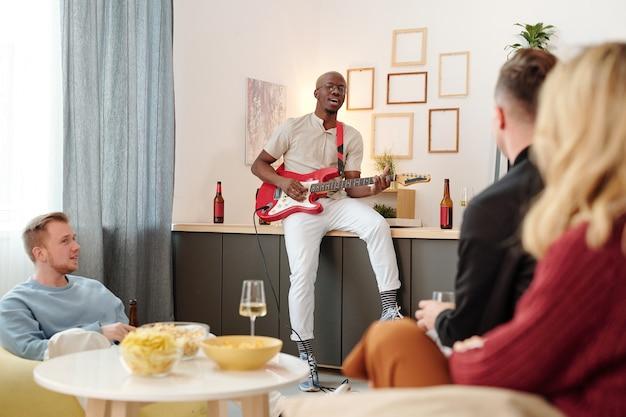 Groupe de jeunes amis interculturels assis près d'une petite table avec des collations et de la flûte et écoutant le chant d'un africain jouant de la guitare à la fête
