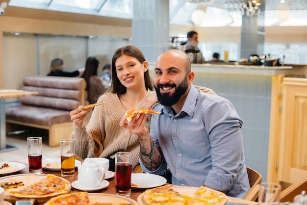 Un groupe de jeunes amis joyeux est assis dans un café à parler et à manger de la pizza