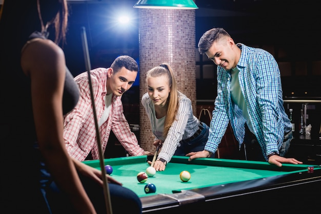 Groupe de jeunes amis joyeux jouant au billard.