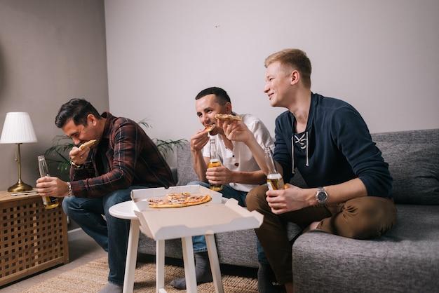 Groupe de jeunes amis mangeant de la pizza parlant et riant sans soucis