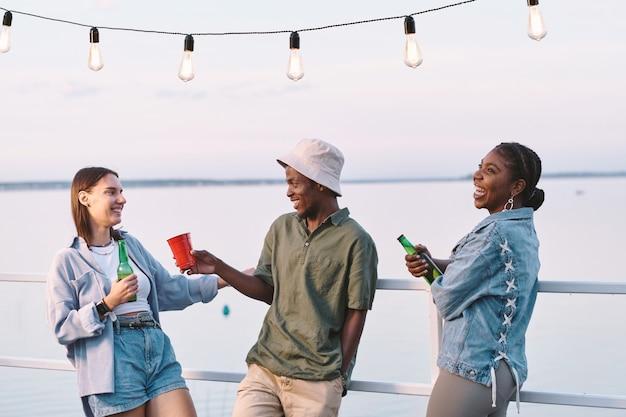 Groupe de jeunes amis multiraciaux avec des boissons s'amusant