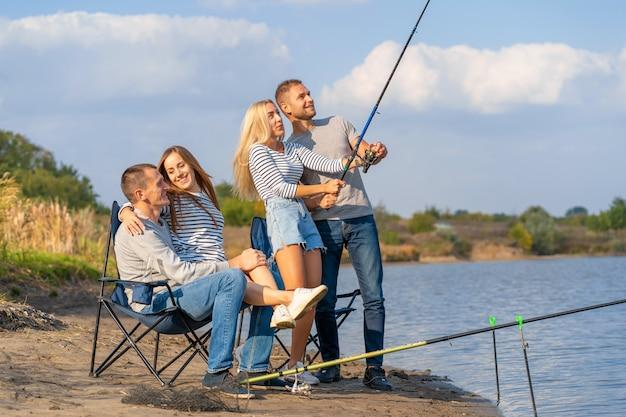 Groupe de jeunes amis pêchant sur la jetée au bord du lac