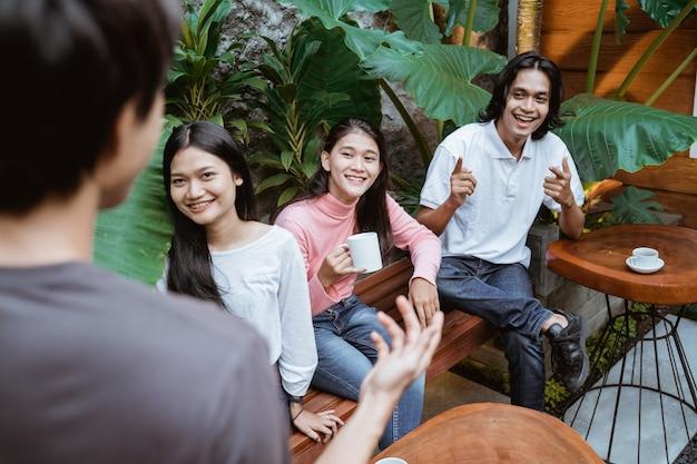 Groupe de jeunes amis prenant un verre sur la terrasse extérieure