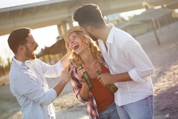 Groupe de jeunes amis riant et buvant de la bière à la plage