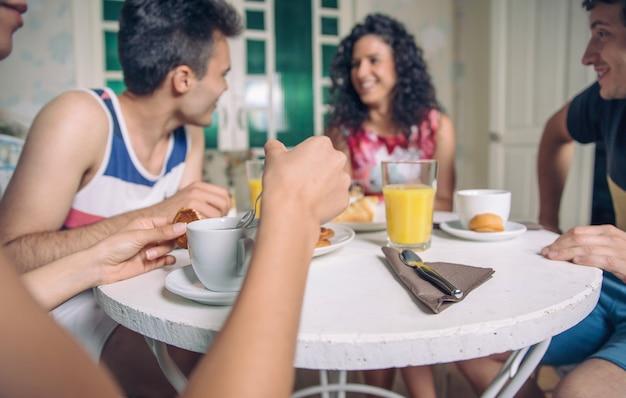Groupe de jeunes amis riant et prenant le petit déjeuner ensemble à la maison. concentrez-vous sur une tasse de café au premier plan.