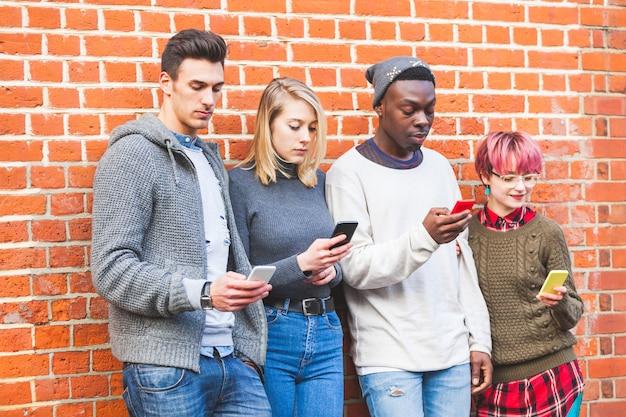 Groupe de jeunes amis avec les téléphones intelligents