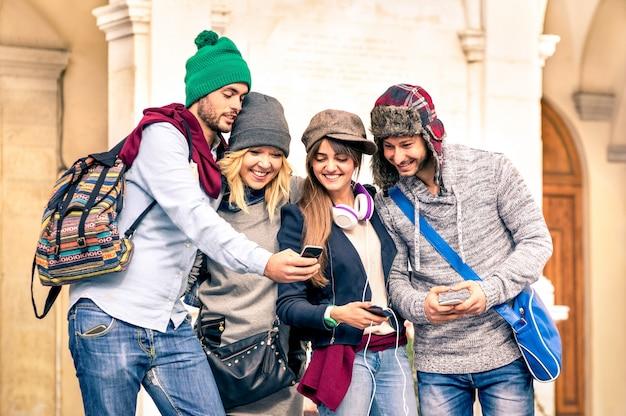 Groupe de jeunes amis touristes hipster s'amusant avec un smartphone dans la vieille ville