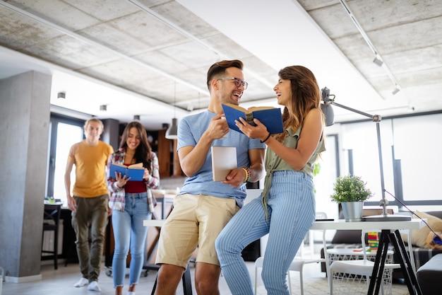 Groupe de jeunes appréciant l'étude de groupe. heureux étudiants universitaires avec des livres et un ordinateur portable pour rechercher des informations pour leur projet.