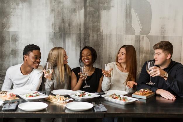 Groupe jeunes, apprécier, dîner, ensemble