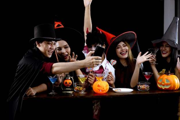 Groupe de jeunes asiatiques en costume célèbrent la fête d'halloween et le selfie sur fond noir. gang d'adolescents asiatiques en cosplay halloween. déguisement fantôme maléfique du groupe ado thaï avec plaisir.