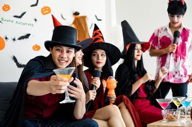 Groupe de jeunes asiatiques en costume de sorcière, l'assistant célèbre la fête avec un verre dans la salle pour le thème halloween. gang teen thai avec fête d'halloween avec le sourire. concept de fête halloween à la maison.