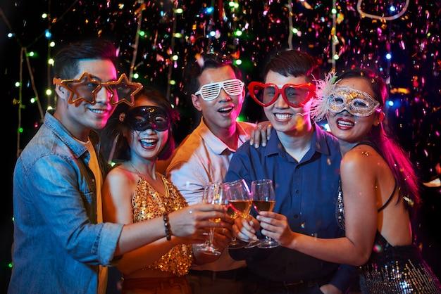 Groupe de jeunes asiatiques joyeux dans de drôles de masques de carnaval debout sous des confettis tombant et grillant avec des verres à vin