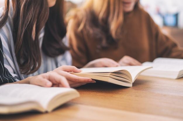 Groupe de jeunes assis et apprécié de lire des livres ensemble sur une table en bois