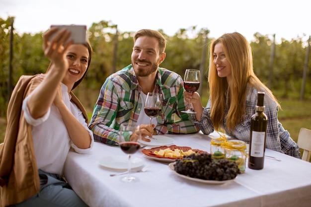 Groupe de jeunes assis à la table et buvant du vin rouge dans le vignoble