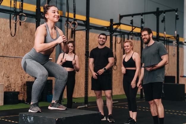 Un groupe de jeunes athlètes dans une salle de sport crossfit faisant une variété de routines d'exercices pendant que l'entraîneur et d'autres membres du groupe les encouragent
