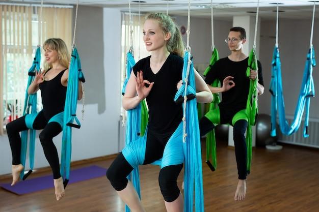 Groupe de jeunes belles femmes yogi faisant la pratique du yoga aérien dans des hamacs dans un club de fitness.