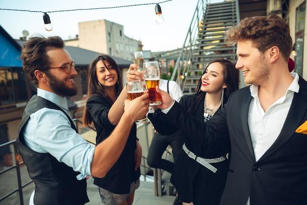 Un groupe de jeunes caucasiens célébrant l'air heureux organise une fête d'entreprise au bureau ou au bar