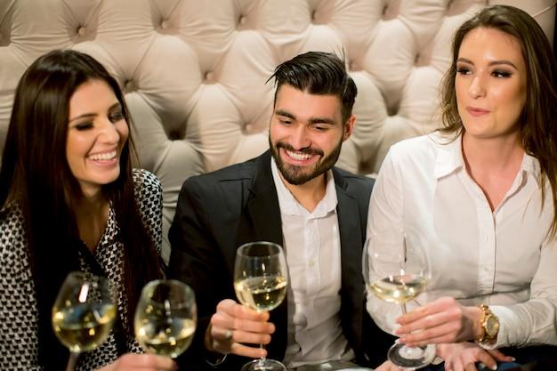 Groupe de jeunes célébrant et grillant avec du vin blanc