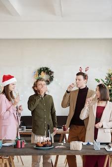 Groupe de jeunes chefs de bureau portant des vêtements décontractés et des bandeaux de noël buvant du champagne dans des flûtes tout en se tenant près d'une table de fête