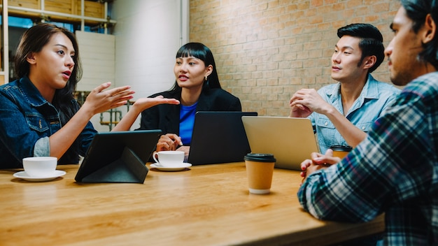 Groupe de jeunes collègues d'affaires asiatiques heureux utilisant un ordinateur portable lors d'une réunion informelle d'équipe, discussion sur le projet de démarrage au café-restaurant.