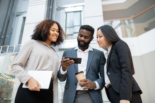 Groupe de jeunes collègues interraciaux utilisant un smartphone dans le couloir tout en surfant sur les médias sociaux pour l'analyse marketing