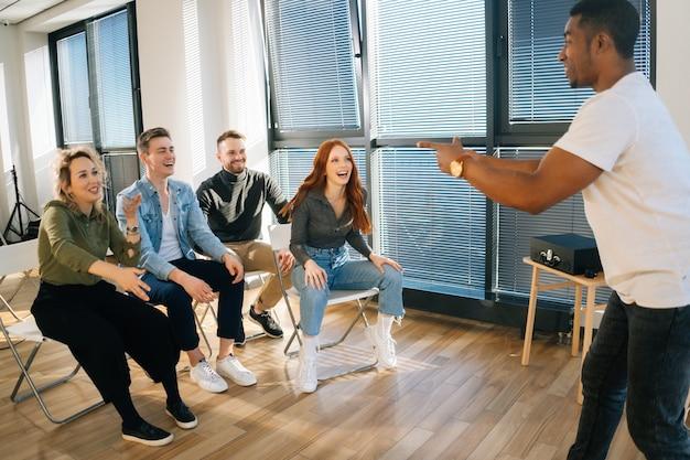 Groupe de jeunes collègues multiethniques divers jouant dans des jeux actifs lors de la constitution d'équipes dans une salle de bureau moderne. joyeux homme afro-américain jouant à des charades avec des amis montrant la pantomime.
