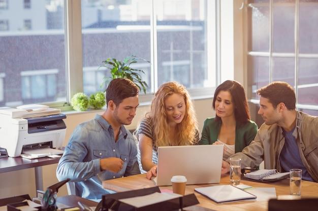 Groupe de jeunes collègues utilisant un ordinateur portable