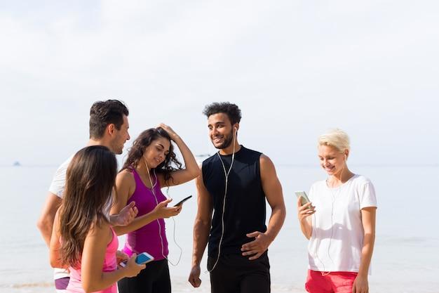 Groupe de jeunes coureurs utilisant un téléphone intelligent