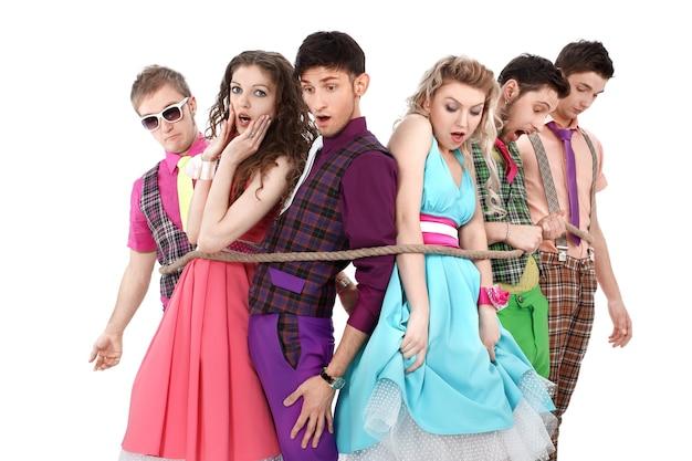 Groupe de jeunes dans des vêtements clairs, attachés avec une corde.isolé sur un mur blanc