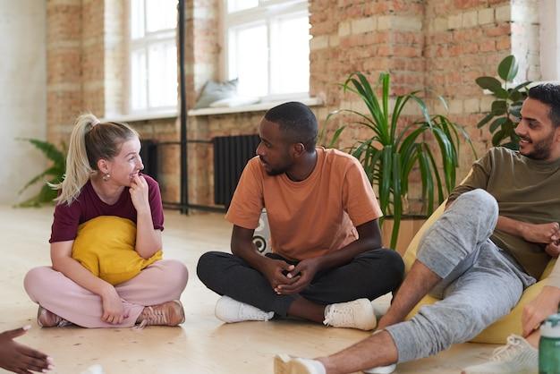 Groupe de jeunes danseurs assis sur le sol et au repos après un entraînement sportif au club de santé