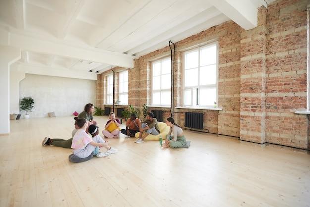 Groupe de jeunes danseurs assis sur le sol se reposer et parler en studio de danse