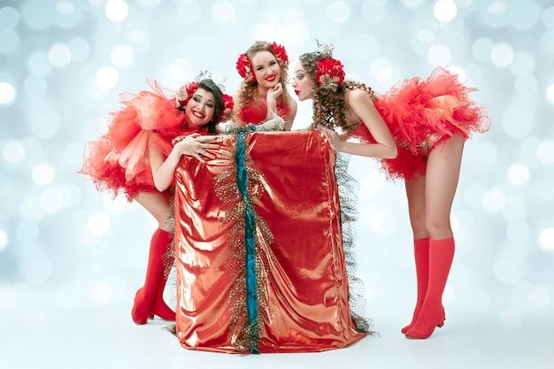 Le groupe de jeunes danseuses souriantes et heureuses avec des robes de carnaval