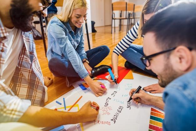 Groupe de jeunes designers créatifs assis sur un sol et prenant des notes sur un grand papier.