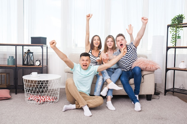 Groupe de jeunes devant la télé. jeunes actifs à la maison encourageant l'équipe. amis gais à l'intérieur s'amuser ensemble.